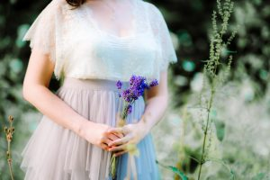 fine art image of a woman wearing a white top and a soft purple skirt, holding lavender. She is standing in a field and her face is not visible.