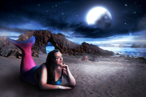 Mermaid in a pink and blue tail on a beach in the moonlight
