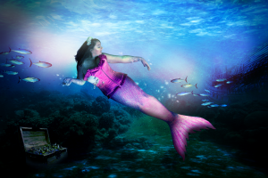 Real mermaid underwater in a pink tail
